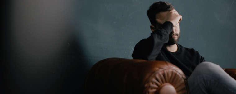 homme assis dans un canapé en cuir épais marron se prenant un air soucieux