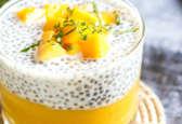 chia pudding à la mangue servi dans un verre à tapas décoré de cubes de mangue