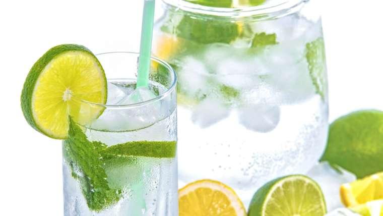 Citronnade à boire en cure detox servie dans un verre à long drink décoré de menthe et de rondelles de citrons jaunes
