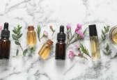 Flacons d'huiles essentielles posées sur un plan en marbre entourées de boutons de fleurs