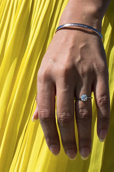 Gros plan main robe jaune plissée bague pierre précieuse